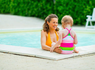 Happy mother and baby girl in swimming pool