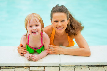Portrait of smiling mother and baby girl in swimming pool