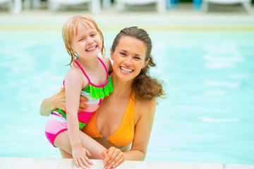 Portrait of mother and baby girl in swimming pool
