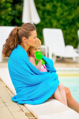 Mother and baby girl wrapped in towel sitting near swimming pool