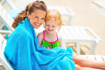 Portrait of happy mother and baby girl wrapped in towel