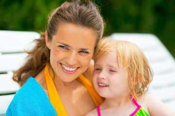 Portrait of happy mother and baby girl sitting on sunbed
