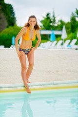 Portrait of happy young woman checking water in swimming pool