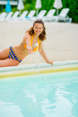 Portrait of happy woman playing with water in swimming pool
