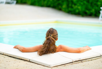Young woman relaxing in swimming pool. rear view