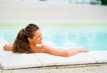 Happy young woman relaxing in swimming pool. rear view
