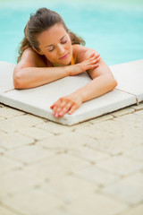 Portrait of calm young woman relaxing in swimming pool