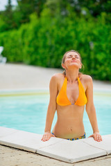 Young woman emerging from swimming pool