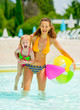 Portrait of mother and baby girl with ball in swimming pool