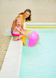 Happy mother and baby girl with ball sitting near swimming pool