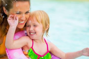 Portrait of happy mother and baby girl swimming in pool