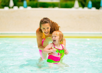 Happy mother and baby girl playing in swimming pool