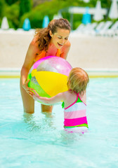 Mother and baby girl playing with ball in swimming pool