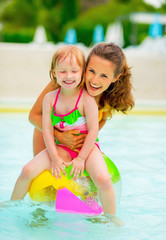 Happy mother and baby girl sitting on ball in swimming pool