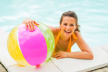 Portrait of smiling young woman with ball in swimming pool