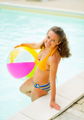 Portrait of smiling woman with ball standing in swimming pool