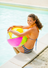 Portrait of smiling woman with ball sitting near swimming pool