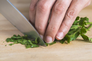 Cocinero picando perejil a cuchillo en la tabla de la cocina