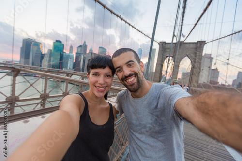 Young Couple Taking Selfie on Brooklyn Bridge - 69839893