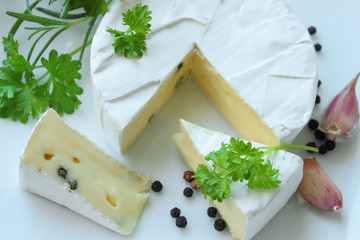Camembert cheese with fresh herbs on a white plate