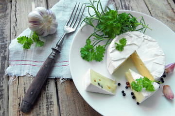 Fresh camembert cheese with herbs on a white plate with fork