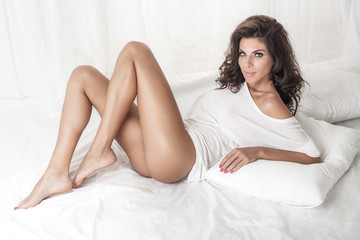 Sensual brunette lady posing in bed