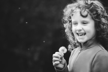 Beautiful little curly girl blowing dandelion, black and white p