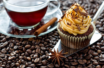 A cup of coffee and a cupcake coffee beans