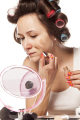 housewife with curlers apply liquid foundation on her face