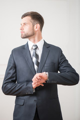 Portrait of handsome confident businessman standing and touching