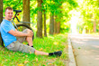man resting against a tree with a bicycle