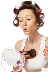 happy housewife with curlers to apply makeup on her cleavage
