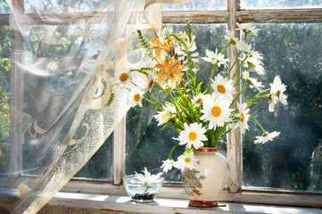 bouquet of chamomilie flowers on the window sill