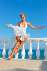 Blonde woman in white dress by the sea in the summer