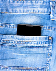 black touch phone in the pocket of blue jeans