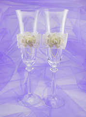 Two beautiful wedding glasses with flowers on a purple backgroun