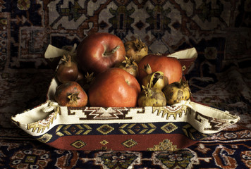 Still life of  pomegranate, apples and carpet