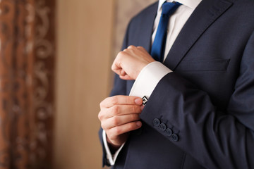 Closeup of a man in black suit correcting a sleeve