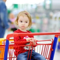 Adorable toddler sitting in shopping cart
