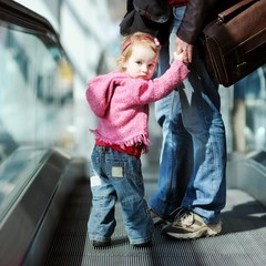 Toddler girl and her father on an escalator