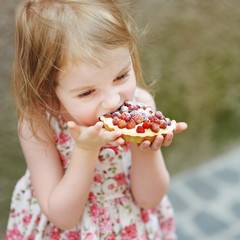 Little girl eating a strawberry tart