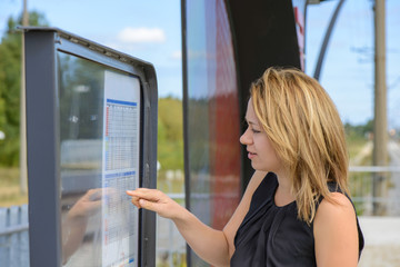 Woman looking a timetable in a station