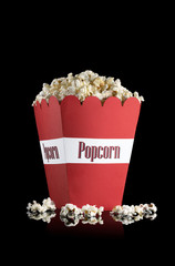 Popcorn in a red paper cup on a black background