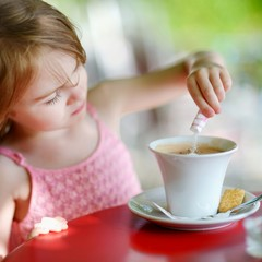Little girl pouring sugar into hot chocolate