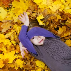 Adorable little girl laying on golden maple leaves