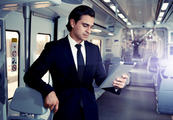 Mature brunette man holding digital tablet working
