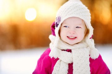 Adorable little girl at sunset on a winter day