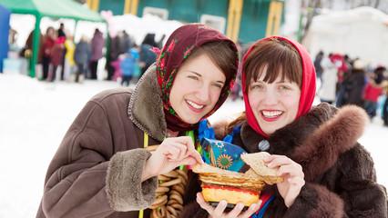 Women  tasting pancake  during  Shrovetide
