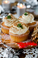 Christmas cupcakes with cream on a table decorated with Christma