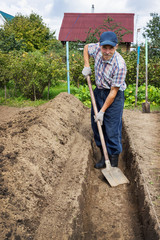 Man digging the earth to build a deep bed of